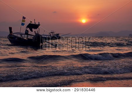 Boat in the wavy sea and sunset at Khlong Muang Beach, Krabi, Thailand.