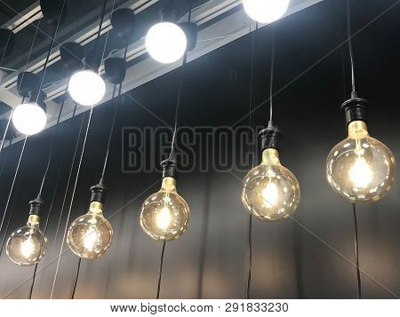 Row Of Hanging Lamp And Light Bulb On Black Background - Side View