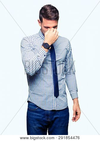 Handsome business man wearing tie tired rubbing nose and eyes feeling fatigue and headache. Stress and frustration concept.
