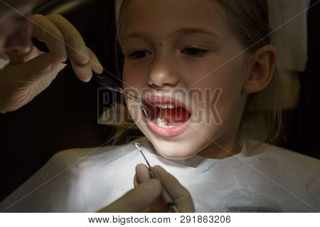 Scared Little Girl At The Dentists Office, In Pain During A Checkup. Pediatric Dental Care And Fear