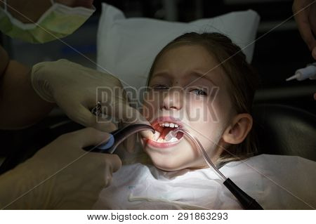 Scared Little Girl At The Dentists Office, In Pain During A Treatment. Pediatric Dental Care And Fea