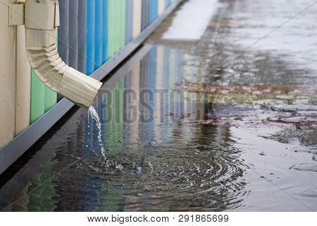 White drainpipe with flooded pavement. Rain water flowing from drain pipe closeup. poster