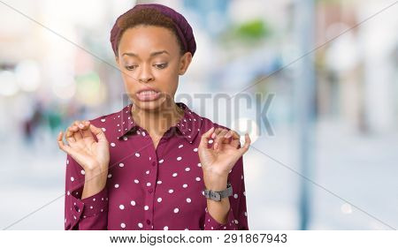 Beautiful young african american woman wearing head scarf over isolated background disgusted expression, displeased and fearful doing disgust face because aversion reaction. With hands raised.
