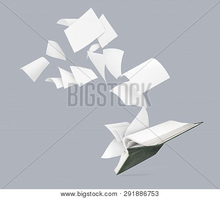An Empty Book With Flying Pages Isolated On A Gray Background