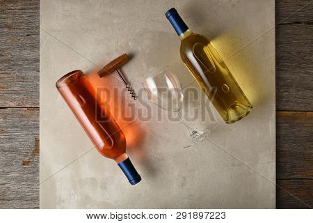 Two bottles of  wine on a gray tile surface on a rustic wood table. A corkscrew and wine glass are between a bottle of white wine and a bottle of blush wine.