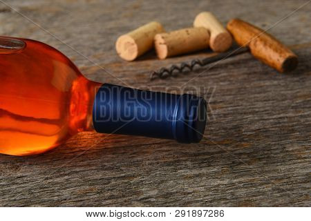 Blush Wine Still Life: Closeup of a bottle of White Zinfandel wine with corkscrew and corks on a rustic wood table.