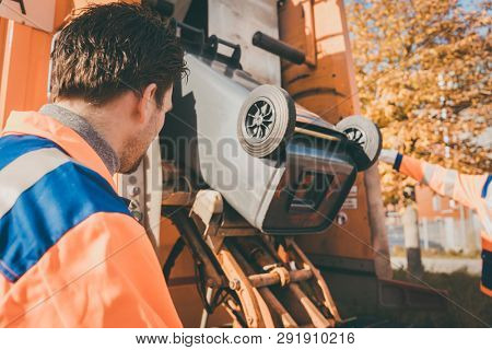 Garbage removal Worker emptying dustbin into waste vehicle