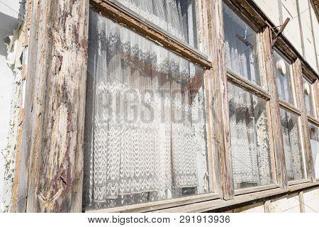 Old Wooden Windows On A Row With White Vintage Curtains In A Village
