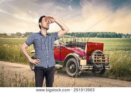 Car Out Of Fuel In A Rural Countryside With A Male In A Blue Shirt Scouting For Help
