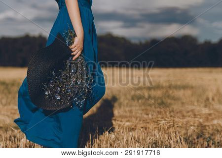 Woman In Blue Dress With A Hat In Her Hand And Bouquet Walks Around The Field At Sunset. The Sky Wit