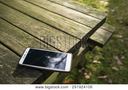 Mobile Phone Is Lying Dangerously On The Edge Of A Wooden Table Carelessly Left With The Possibility