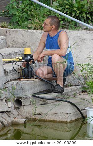 Człowiek z pompa wody do podlewania ogrodu, w pobliżu stawu.W pobliżu Kiev, Ukraina