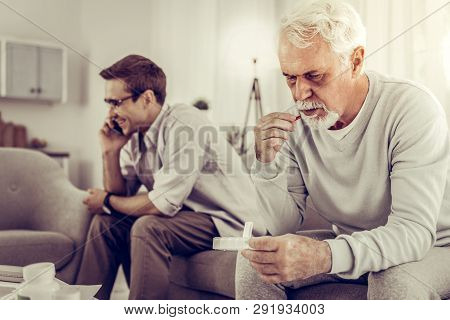 Old Man Taking Pills While Son Indifferently Having A Phone Call.