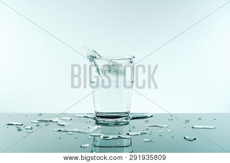 Glass Of Pure Fresh Water With Ice Cube.reflection Of Crystal Glass From The Table On White Backgrou