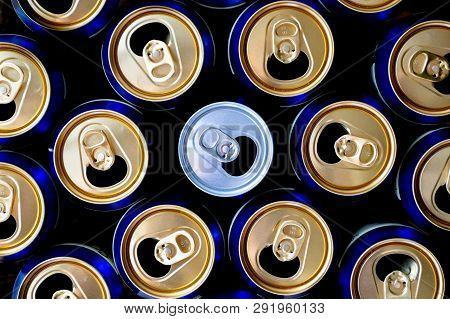 Abstract Pattern Of Opened Aluminium Cans, Top View. One White Soda Or Beer Can Standing Out Among Y