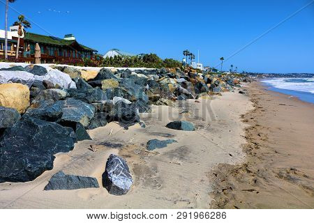 March 20, 2019 In Malibu, Ca:  People Walking On The Beach Besides Homes Overlooking The Pacific Oce