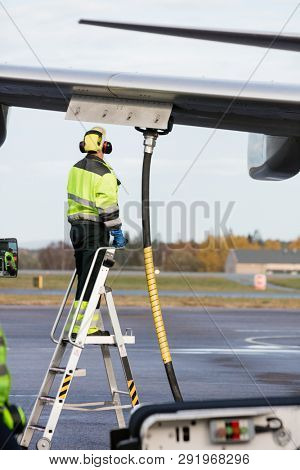 Male Worker Refueling Airplane While Standing On Ladder