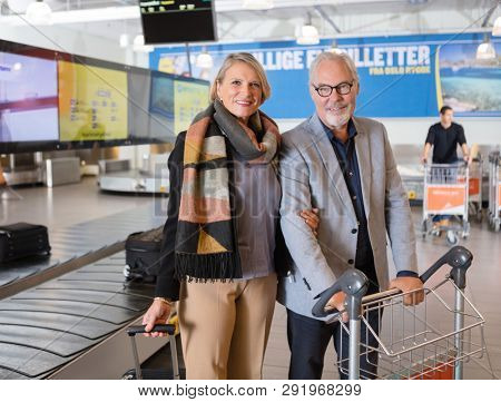 Happy Senior Business Couple Standing By Conveyor Belt At Airpor