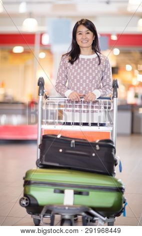 Happy Mid Adult Woman With Luggage In Cart At Airport
