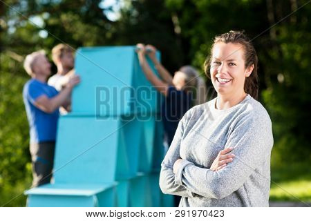 Smiling Woman Standing Arms Crossed While Friends Making Planks