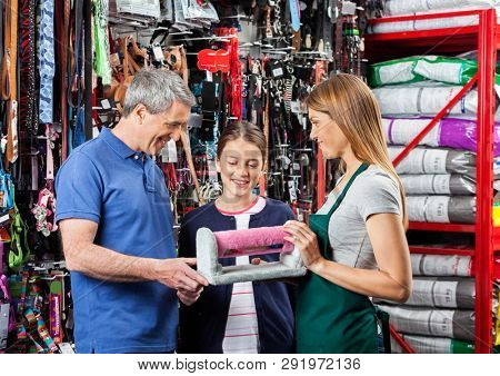 Father And Daughter Buying Pet Cat Scratcher From Saleswoman