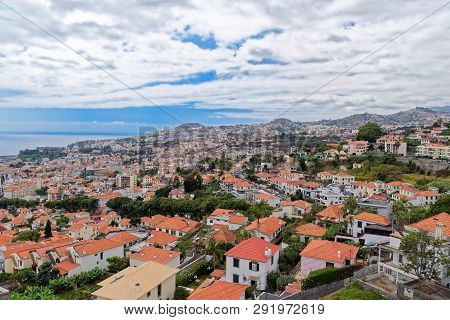 Panorama View At Traditional Houses Against Blue Cloudy Sky On Madeira Island. Funchal City, Portuga