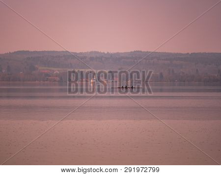 Image Of Lake Ammer With Rowing Boat And Village With Church In The Background During Sunset