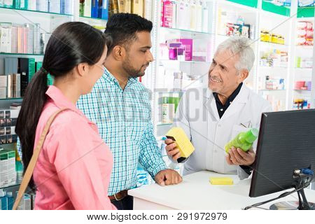 Pharmacist Showing Products To Couple At Checkout Counter