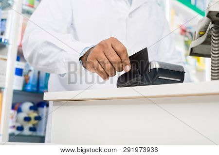 Midsection Of Pharmacist Swiping Credit Card On Reader