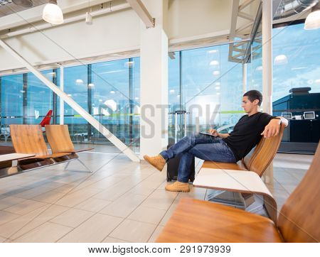 Young Man Using Laptop At Airport Lobby