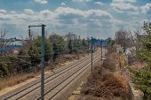 Train tracks running through outskirts of small town on sunny day with puffy cumulus clouds in sky. poster