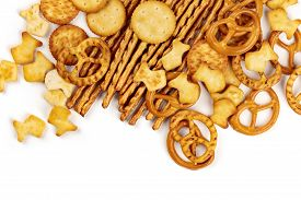 Many Salty Crackers, Sticks, Pretzels, And Gold Fishes, Shot From The Top On A White Background With