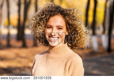 Hairstyle curly hair, portrait of a young beautiful girl in an autumn park