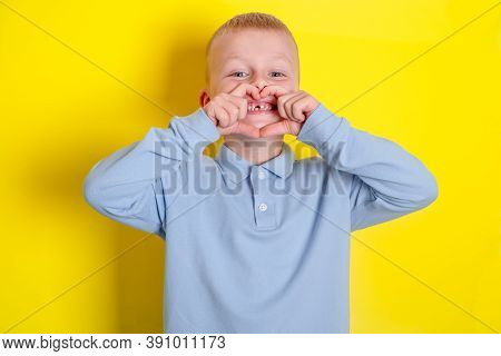 The Childs Hands Show The Heart, Child Smile Without Upper Baby Tooth. Health Care, Dental Hygiene.