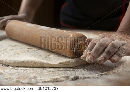 Baker kneading dough for pizza preparation. Chef cook making dough for baking pie on wooden table. P