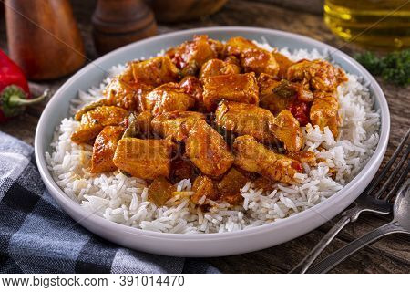 A Plate Of Delicious Creole Cajun Style Chicken With White Rice.