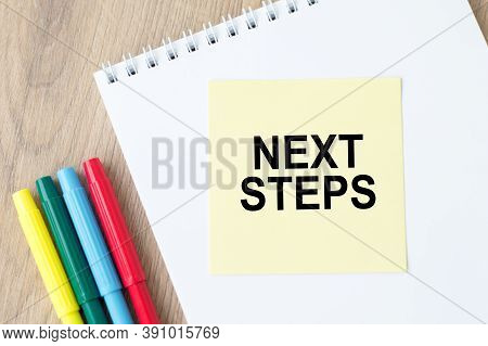 Next Steps Inscription On The Sticker On An Open Notebook On The Table Next To Colored Markers