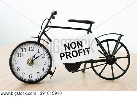 Card With The Inscription Non Profit On The Clock On A Light Background On The Table.