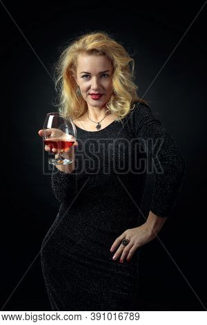 Attractive Mature Woman In Black Evening Dress With A Snifter Of Brandy. Beautiful Forty Years Blond