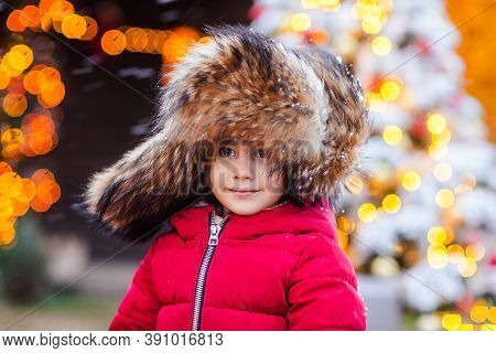 Portrait Of Young Pretty Girl In Traditional Russian Fur Cap With Ear Flaps And Red Winter Jacket Ag