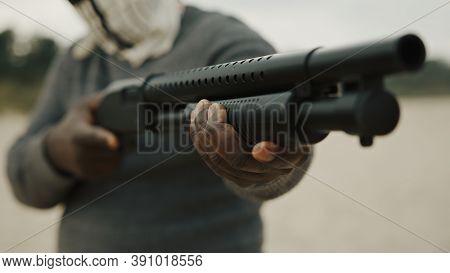 Terrorist Pumps A Shotgun To Start Shooting. High Quality Photo
