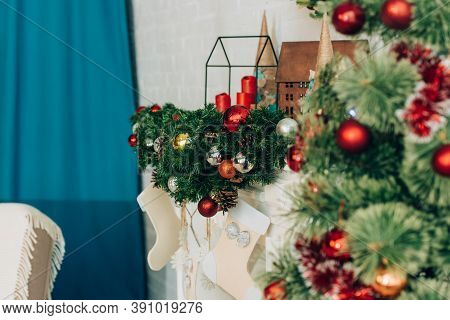 Decorated Branches With Baubles And Candles Near Fireplace
