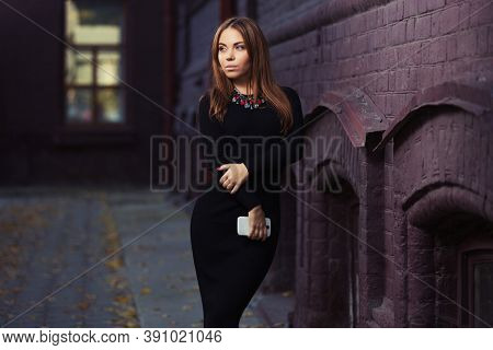Young woman with a cell phone walking on city street Stylish fashion model with long straight hair in black sweater dress