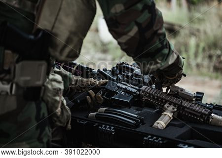 Military Man With Gun Case Takes Out An Assault Rifle In Destroyed City. Military And Rescue Operati