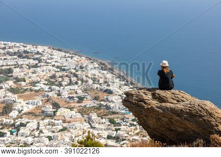A View From The Back Of A Girl In A Hat Sits On A Mountain And Admires The Beautiful View Of The Aeg