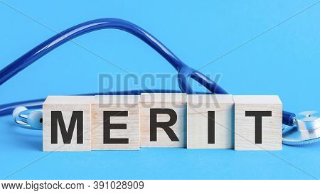 Merit Word Written On Wooden Blocks And Stethoscope On Light Blue Background