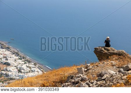 Santorinir, Greece- 18 September 2020: A View From The Back Of A Girl In A Hat Sits On A Mountain An