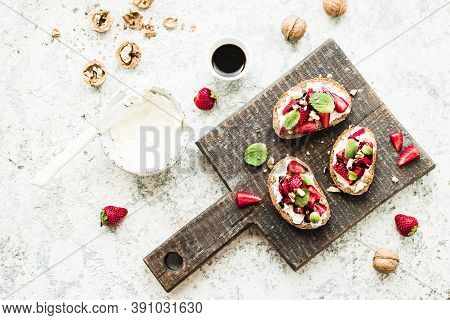 Sandwich With Strawberries, Soft Cheese, Nuts, Mint And Balsamic Vinegar On Wooden Board On Grey Bac