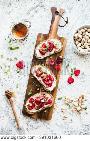 Sandwich With Strawberries, Soft Cheese, Pistachios, Mint And Honey On Wooden Board On Grey Backgrou