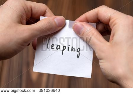 Concept Of Cancelling. Hands Closeup Tearing A Sheet Of Paper With Inscription Leaping